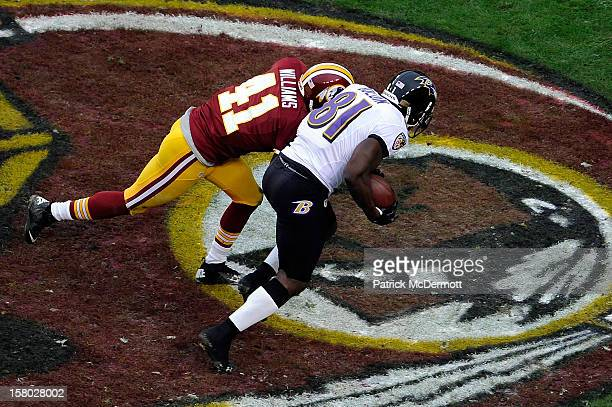 Anquan Boldin of the Baltimore Ravens is tackled by Madieu Williams of the Washington Redskins after catching a pass for a touchdown in the first...