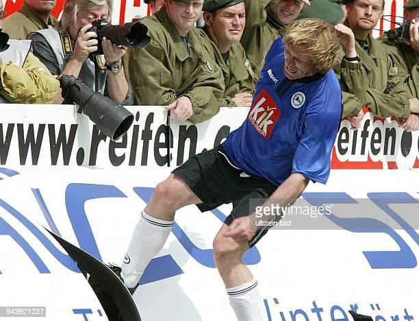 Ansgar Brinkmann Mittelfeldspieler DSC Arminia Bielefeld D tritt gegen eine Werbebande beobachtet von Polizisten und Fotografen