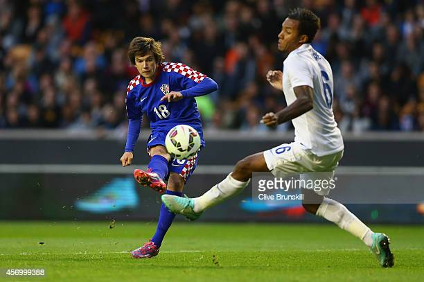 Ante Coric of Croatia shoots past Liam Moore of England during the UEFA U21 Championship Playoff First Leg match between England and Croatia at...