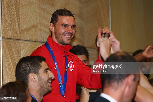 Ante Covic of the Western Sydney Wanderers waves to supporters as he arrives at Sydney International Airport from Saudi Arabia after victory over Al...