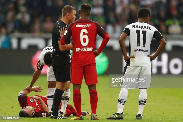Ante Rebic of Frankfurt lies injured on the pitch while Lars Stindl of Moenchengladbach check on him Jonathan de Guzman of Frankfurt talks to referee...