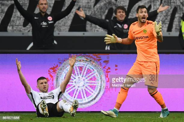 Ante Rebic of Frankfurt lies on the pitch after a foul by goalkeeper Roman Buerki of Dortmund which resulted in a penalty for Frankfurt during the...