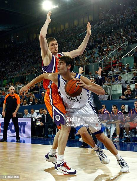 Ante Tomic #4 of Real Madrid competes with Serhiy Lischuk #12 of Power Electronics Valencia during the PlayOffs Date 5 game between Real Madrid vs...