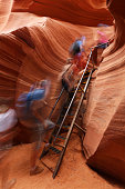 Long exposure motion blur of people climbing ladder in Lower Antelope Canyon. Page, Arizona.