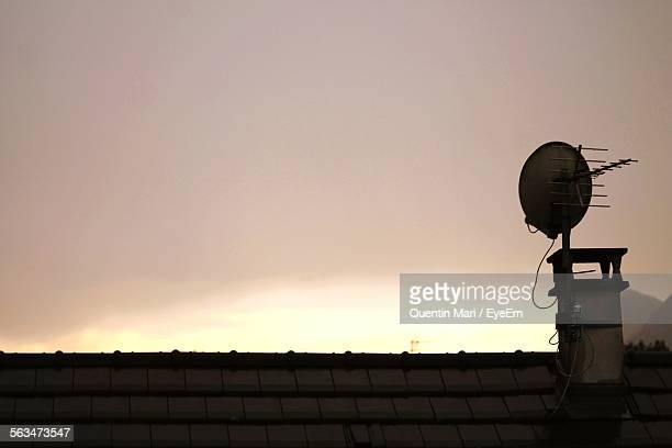 Antenna On House Roof Against Sky During Sunset