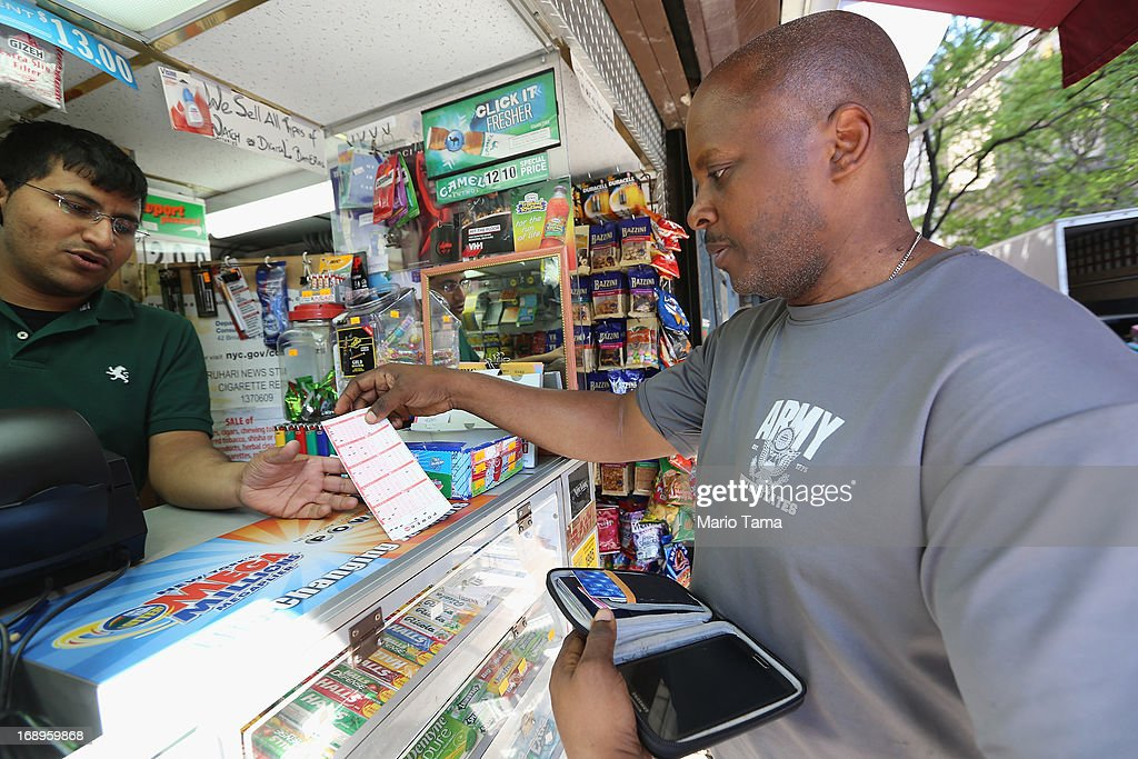 Anthony Adams (R) purchases Powerball tickets in Manhattan on May 17, 2013 in New York City. The Powerball lottery jackpot has crossed $600 million and is now the largest prize in Powerball history and second largest in the world.