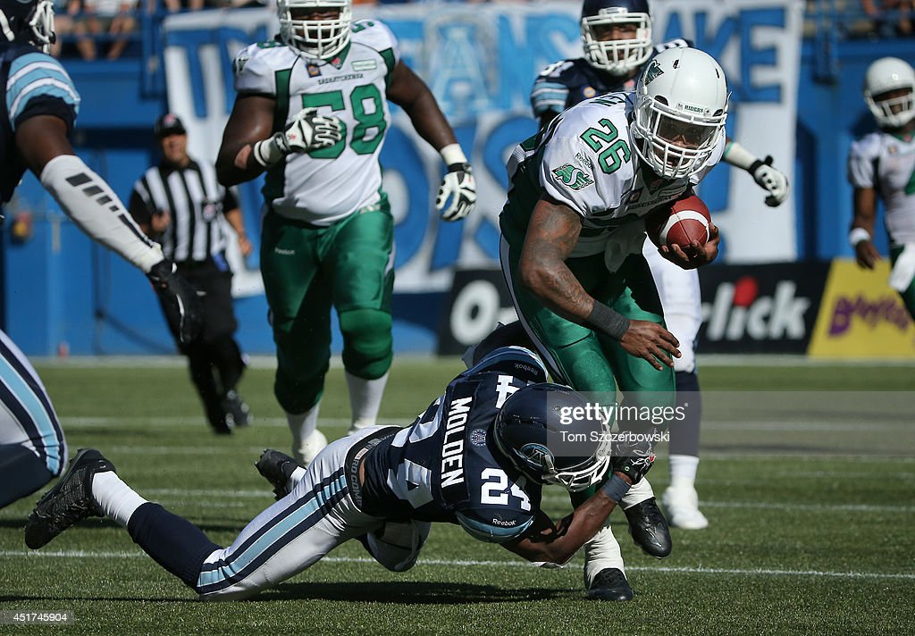 Anthony Allen #26 of the Saskatchewan Roughriders is tackled by Antwuan Molden #24 of the Toronto Argonauts during a CFL game on July 5, 2014 at Rogers Centre in Toronto, Ontario, Canada.