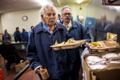 Anthony Alvarez age 82 waits in line for breakfast while being assisted by Phillip Burdick a fellow prisoner and member of the Gold Coats program at...