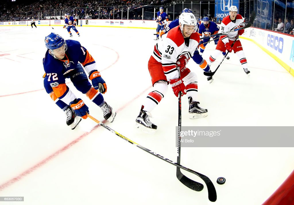Anthony Beauvillier #72 of the New York Islanders and Derek Ryan #33 of the Carolina Hurricanes battle for the puck during their game at the Barclays Center on March 13, 2017 in New York City.
