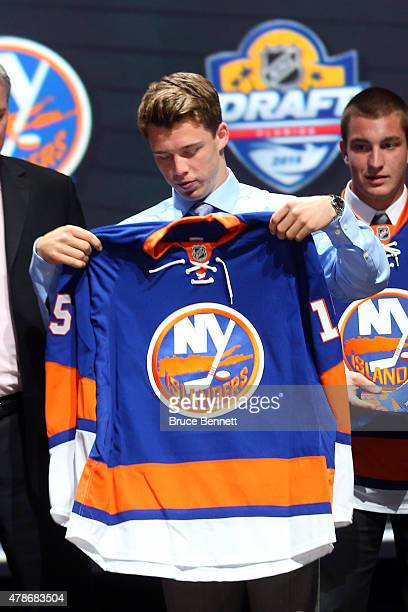 Anthony Beauvillier puts on his jersey after being selected 28th overall by the New York Islanders in the first round of the 2015 NHL Draft at BBT...