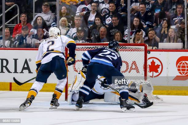 Anthony Bitetto of the Nashville Predators watches as Chris Thorburn of the Winnipeg Jets redirects a shot just wide of the net during third period...