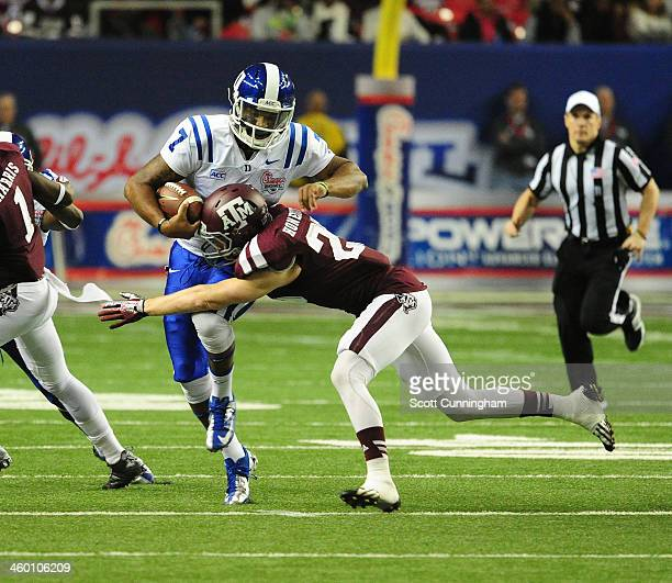 Anthony Boone of the Duke Blue Devils is tackled by Clay Honeycutt of the Texas AM Aggies during the ChickFilA Bowl at the Georgia Dome on December...