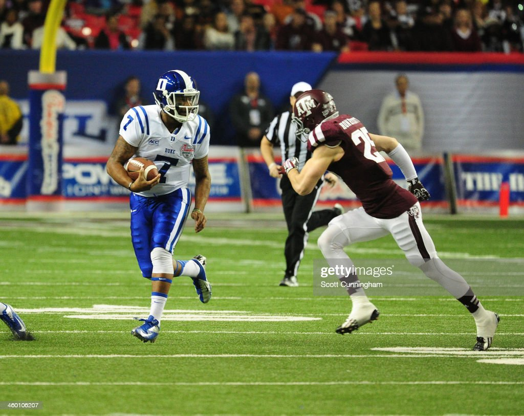 Anthony Boone of the Duke Blue Devils scrambles against the Texas AM Aggies during the ChickFilA Bowl at the Georgia Dome on December 31 2013 in...