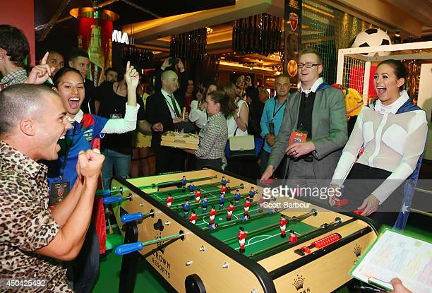 Anthony Callea celebrates as he scores a goal as Jesinta Campbell reacts at the Crown's Celebrity Foosball Cup on June 11 2014 in Melbourne Australia