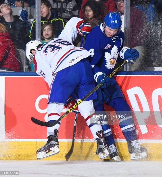 Anthony Camara of the St John's IceCaps puts a hit on Justin Holl of the Toronto Marlies during AHL game action on April 4 2017 at Ricoh Coliseum in...