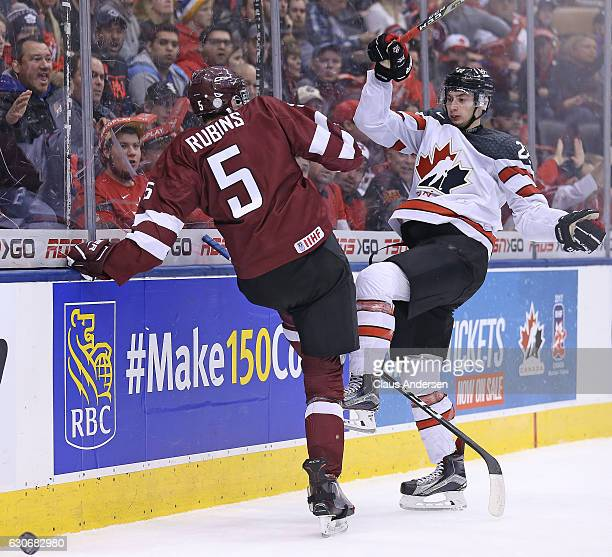 Anthony Cirelli of Team Canada gets bumped by Kristians Rubins of Team Latvia during a preliminary game in the 2017 IIHF World Junior Hockey...