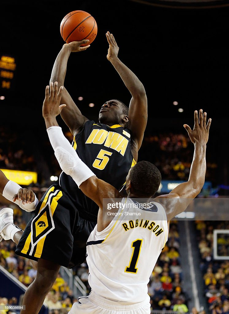 Anthony Clemmons #5 of the Iowa Hawkeyes gets off a second half shot behind Glenn Robinson III #1 of the Michigan Wolverines at Crisler Center on January 6, 2013 in Ann Arbor, Michigan. Michigan won the game 95-67.