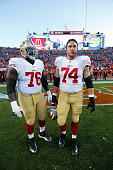 Anthony Davis and Joe Staley of the San Francisco 49ers stand on the field prior to the game against the Denver Broncos at Sports Authority Field at...