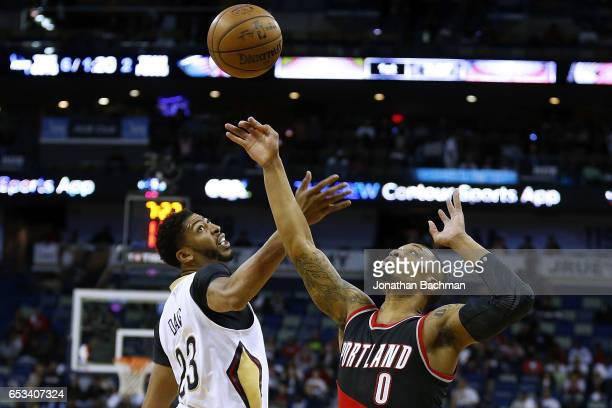 Anthony Davis of the New Orleans Pelicans and Damian Lillard of the Portland Trail Blazers go for a loose ball during the first half of a game at the...