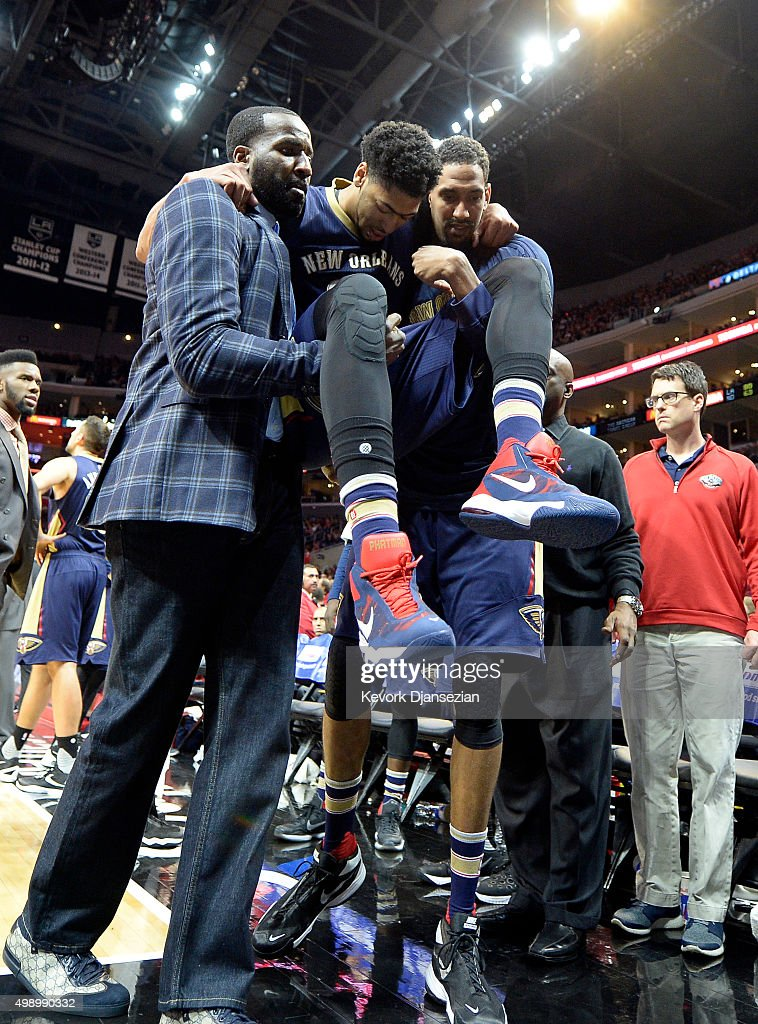 Anthony Davis #23 of the New Orleans Pelicans carried off the field by his teammates Kendrick Perkins #5 and Alexis Ajinca #42 after injuring his right knee following a collision with Chris Paul #3 of the Los Angeles Clippers during the third quarter the basketball game at Staples Center November 27, 2015, in Los Angeles, California.
