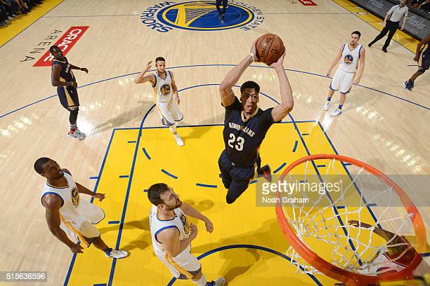 Anthony Davis of the New Orleans Pelicans dunks against Andrew Bogut of the Golden State Warriors on March 14 2016 at Oracle Arena in Oakland...