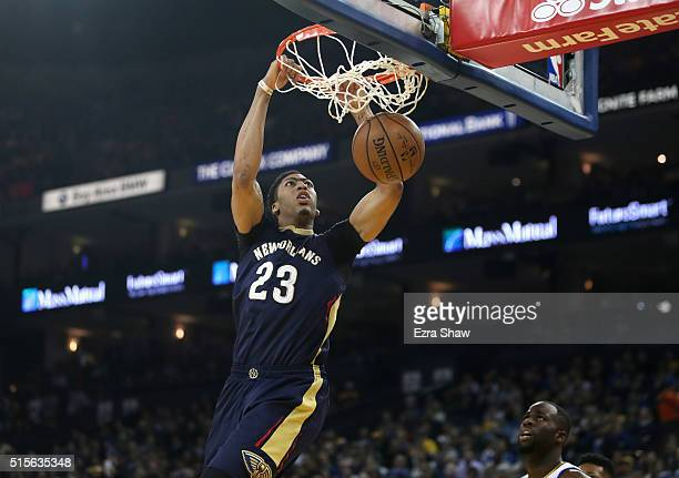 Anthony Davis of the New Orleans Pelicans dunks the ball over Draymond Green of the Golden State Warriors at ORACLE Arena on March 14 2016 in Oakland...