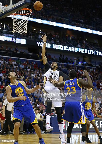 Anthony Davis of the New Orleans Pelicans shoots over Draymond Green of the Golden State Warriors and Zaza Pachulia during the first half of a game...