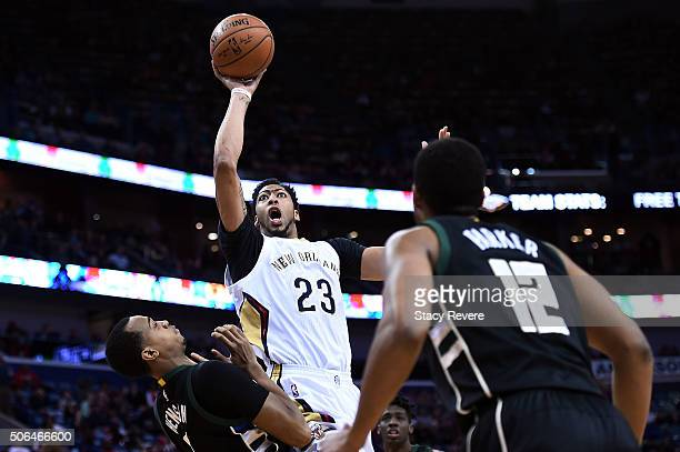 Anthony Davis of the New Orleans Pelicans shoots over John Henson of the Milwaukee Bucks during the first half of a game at the Smoothie King Center...