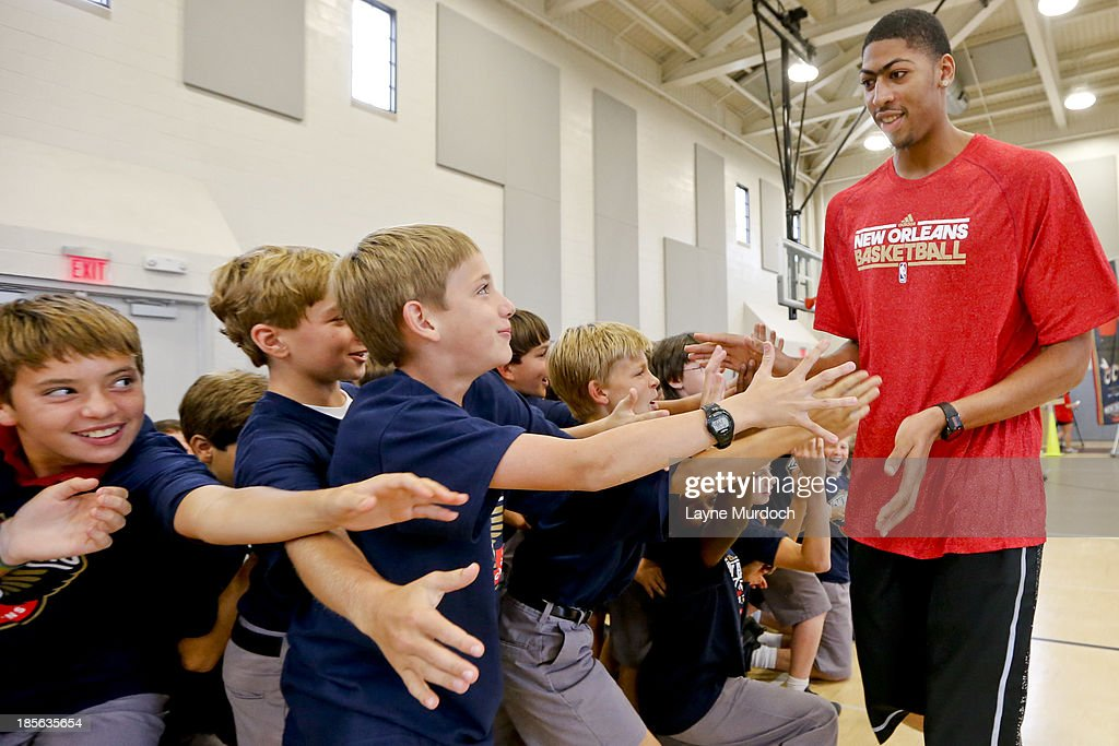 Anthony Davis of the New Orleans Pelicans slaps hands with students as the team partnered with Ochsner Health System, Blue Cross Blue Shield of Louisiana and the Louisiana Campaign for Tobacco-Free Living (TFL) celebrate the launch of the Pelicans Junior Training Camp program on October 21, 2013 at Christian Brothers School in New Orleans, Louisiana.
