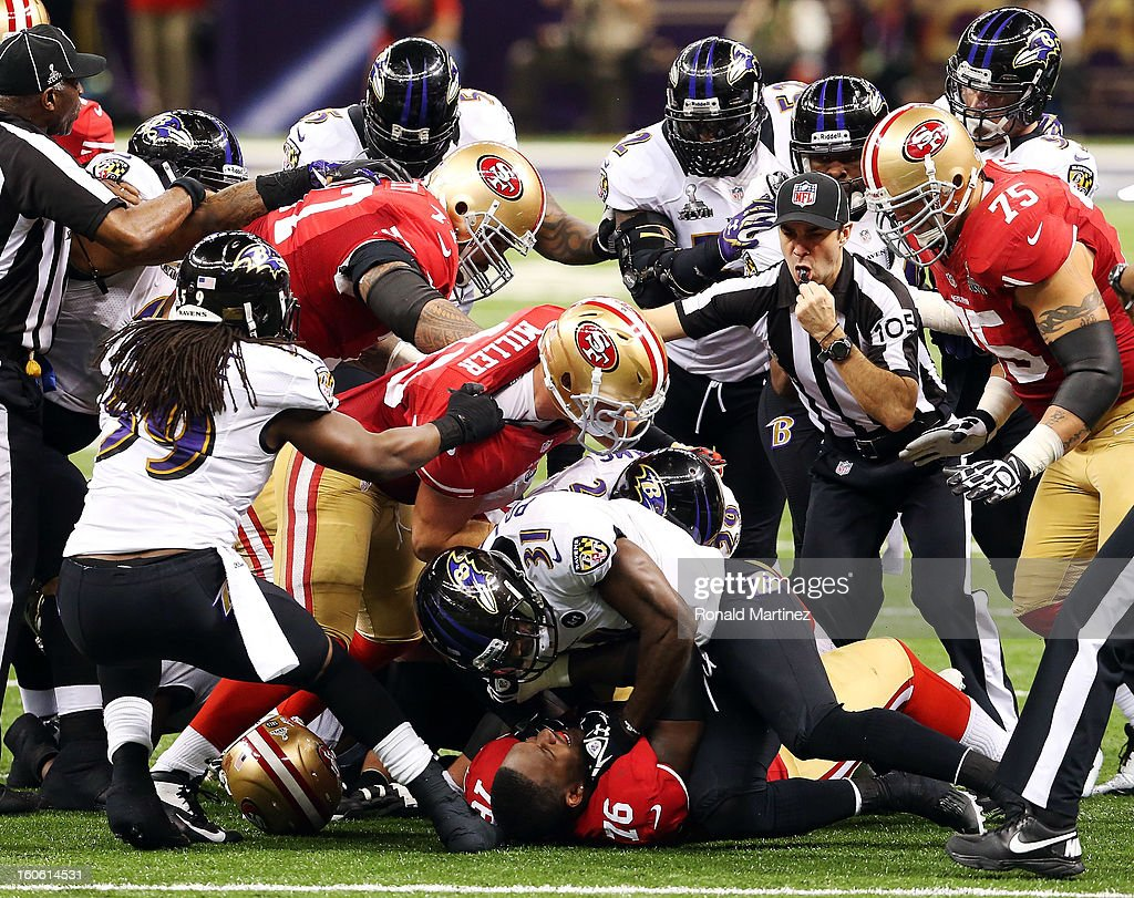 Anthony Davis #76 of the San Francisco 49ers and Bernard Pollard #31 of the Baltimore Ravens get rough with each other at the bottom of a pile in the second quarter during Super Bowl XLVII at the Mercedes-Benz Superdome on February 3, 2013 in New Orleans, Louisiana.
