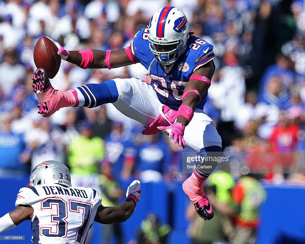 Anthony Dixon #26 of the Buffalo Bills hurtles Alfonzo Dennard #37 of the New England Patriots during the first half at Ralph Wilson Stadium on October 12, 2014 in Orchard Park, New York.
