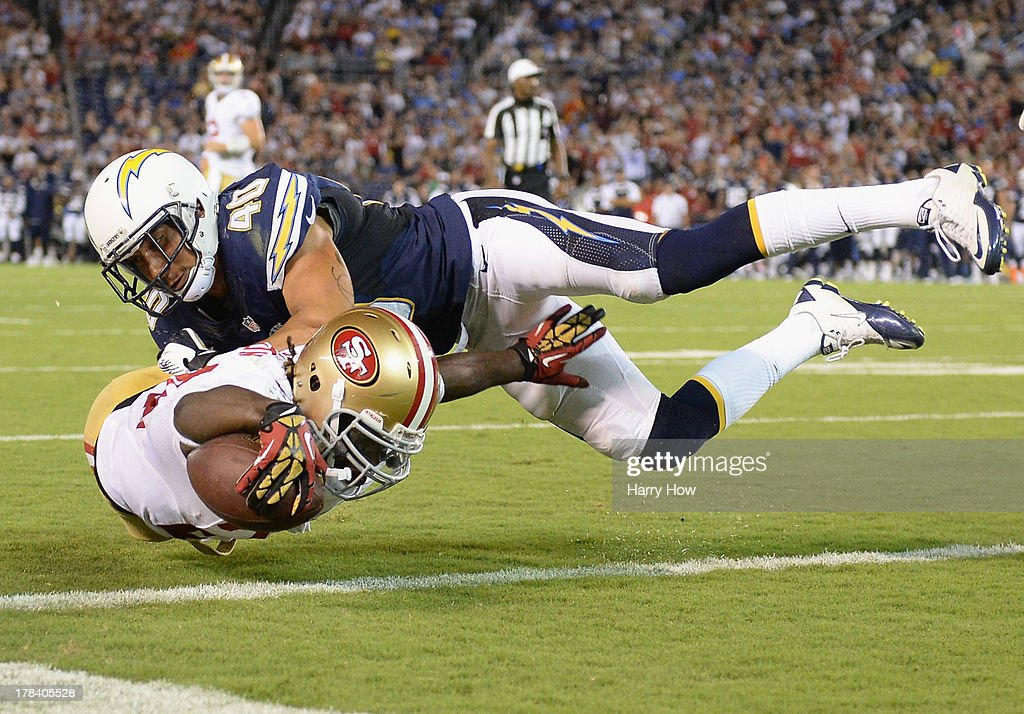 Anthony Dixon of the San Francisco 49ers dives for the endzone for a touchdown as he is hit by Sean Cattouse of the San Diego Chargers during a...