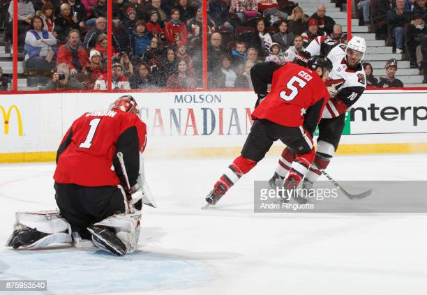 Anthony Duclair of the Arizona Coyotes shoots the puck against Cody Ceci and Mike Condon of the Ottawa Senators scoring the overtime winning and a...