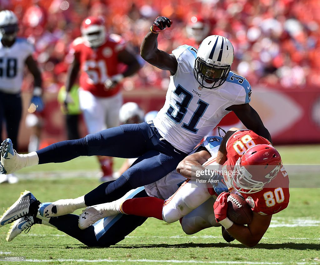 Anthony Fasano #80 of the Kansas City Chiefs is tackled by Michael Griffin and Bernard Pollard #31 of the Tennessee Titans during the second half at Arrowhead Stadium on September 7, 2014 in Kansas City, Missouri.