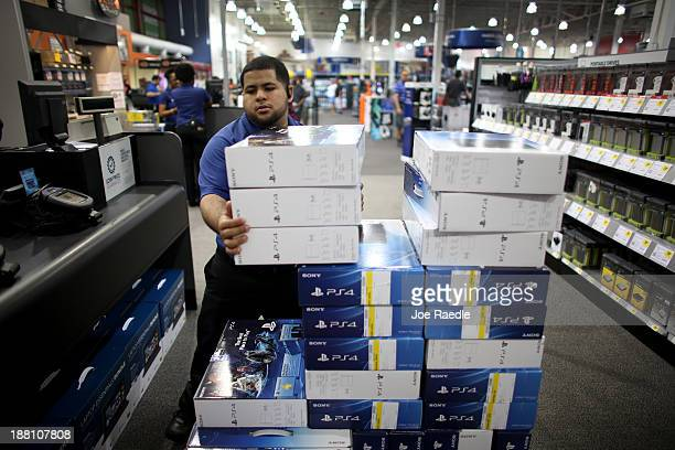 Anthony Feliz sales associate unloads a supply of Sony Playstation 4 consoles at Best Buy after they went on sale at midnight on November 15 2013 in...