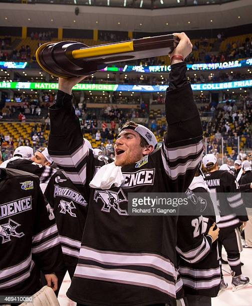 Anthony Florentino of the Providence College Friars raises the national championship trophy after a 43 Friar win against the Boston University...