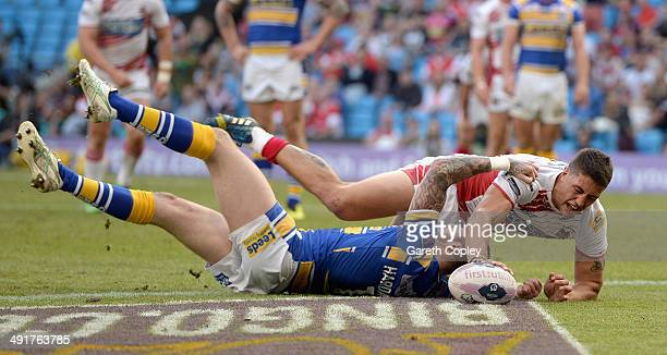 Anthony Gelling of Wigan Warriors scores the opening try past Zak Hardaker of Leeds Rhinos during the Super League match between Wigan Warriors and...