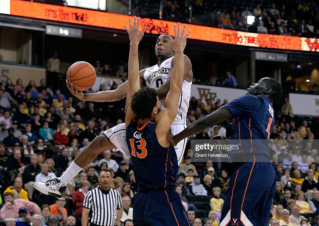 Anthony Gill of the Virginia Cavaliers defends a drive by Codi MillerMcIntyre of the Wake Forest Demon Deacons during their game at the LJVM Coliseum...
