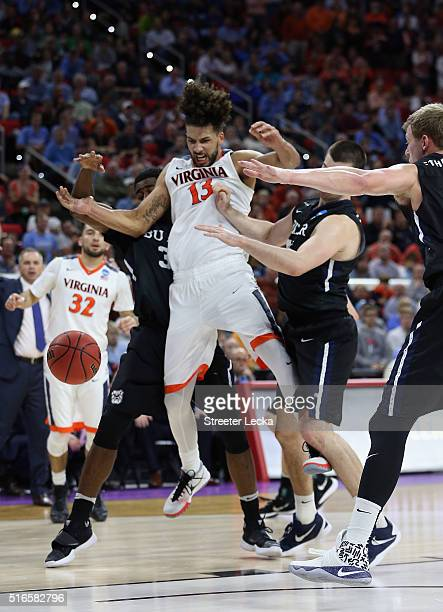 Anthony Gill of the Virginia Cavaliers fights for possession of the ball against Kelan Martin Andrew Chrabascz and Austin Etherington of the Butler...