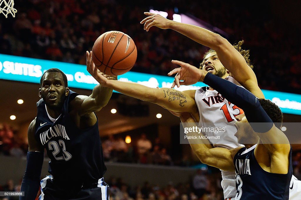 Anthony Gill #13 of the Virginia Cavaliers shoots the ball against <a gi-track='captionPersonalityLinkClicked' href=/galleries/search?phrase=Josh+Hart+-+Basketball+Player&family=editorial&specificpeople=12558291 ng-click='$event.stopPropagation()'>Josh Hart</a> #3 and <a gi-track='captionPersonalityLinkClicked' href=/galleries/search?phrase=Daniel+Ochefu&family=editorial&specificpeople=9986325 ng-click='$event.stopPropagation()'>Daniel Ochefu</a> #23 of the Villanova Wildcats in the second half during a game at John Paul Jones Arena on December 19, 2015 in Charlottesville, Virginia. The Virginia Cavaliers defeated the Villanova Wildcats 86-75.