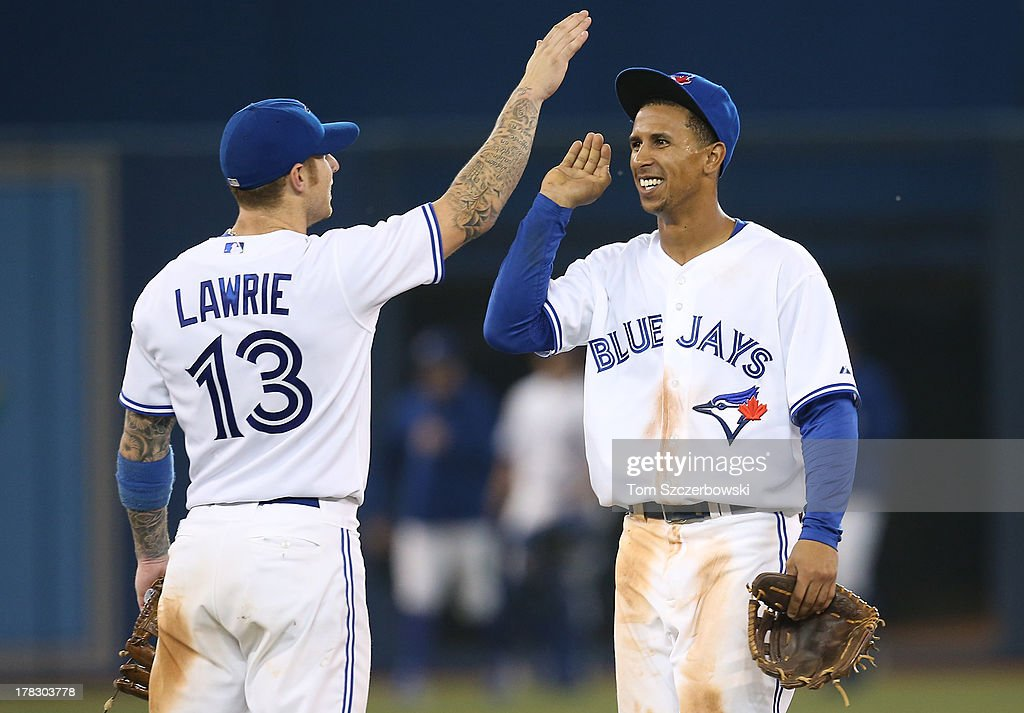 Anthony Gose #8 of the Toronto Blue Jays celebrates their victory with Brett Lawroe #13 during MLB game action against the New York Yankees on August 28, 2013 at Rogers Centre in Toronto, Ontario, Canada.