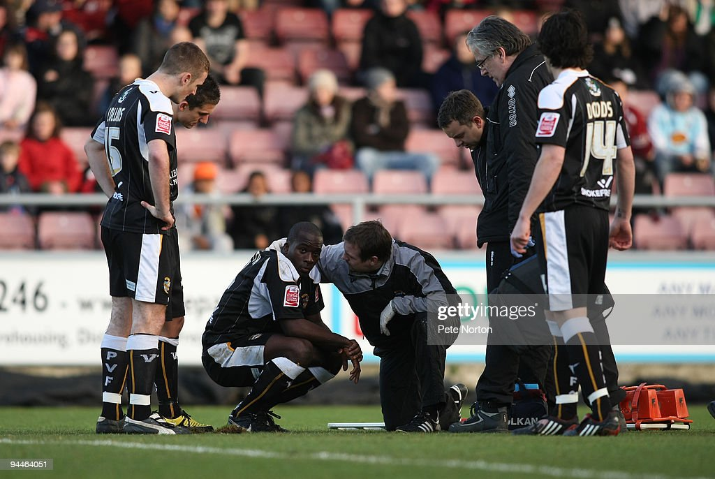 Anthony Griffith of Port Vale receives treatment from physio John Bower after being knocked unconscious as his team mates look on during the Coca Cola League Two Match between Northampton Town and Port Vale at Sixfields Stadium on December 12, 2009 in Northampton, England.