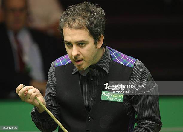 Anthony Hamilton of England chalks his cue during his match against Stephen Maguire of Scotland during day six of the 888com World Snooker...