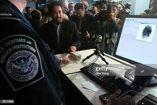 Anthony Ho Supervisory Special Agent of the USVISIT Program demonstrates the process of inkless fingerprints scanning during a news conference on the...