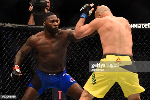 Anthony Johnson punches Glover Teixeira of Brazil in their light heavyweight bout during the UFC 202 event at TMobile Arena on August 20 2016 in Las...