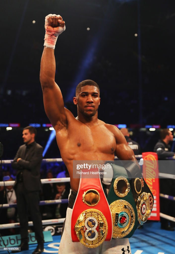 Anthony Joshua celebrates victory with his belts after a 10th round stoppage during the IBF, WBA & IBO Heavyweight Championship contest against Carlos Takam at Principality Stadium on October 28, 2017 in Cardiff, Wales.