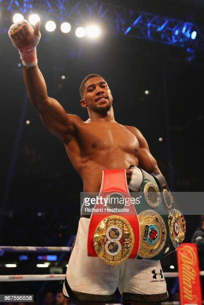 Anthony Joshua celebrates victory with his belts after a 10th round stoppage during the IBF WBA IBO Heavyweight Championship contest against Carlos...