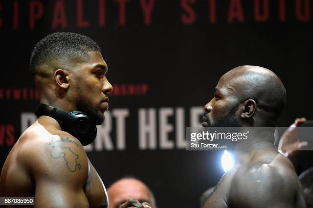 Anthony Joshua of England and Carlos Takam of France face each other during a weighin prior to tomorrow's world heavyweight title fight between...