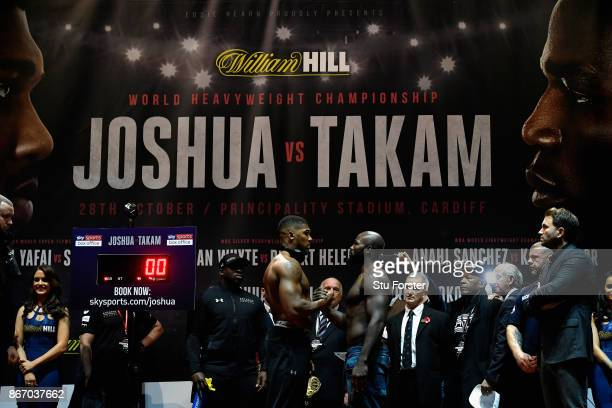 Anthony Joshua of England and Carlos Takam of France face each other with a hand shake during a weighin prior to tomorrow's world heavyweight title...