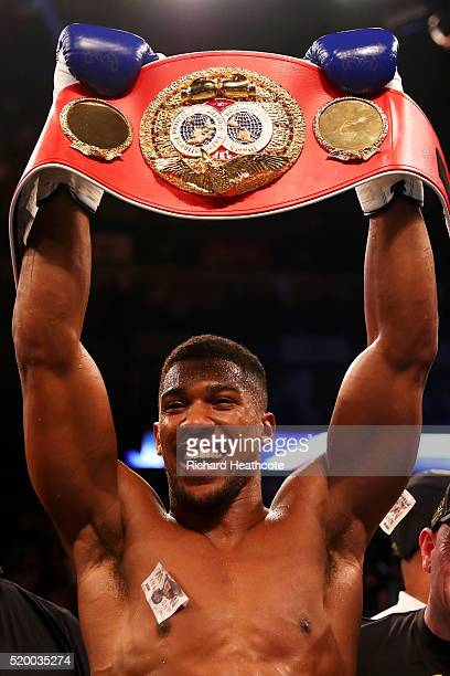 Anthony Joshua of England celebrates with the belt and his team after defeating Charles Martin of the United States in action during the IBF World...